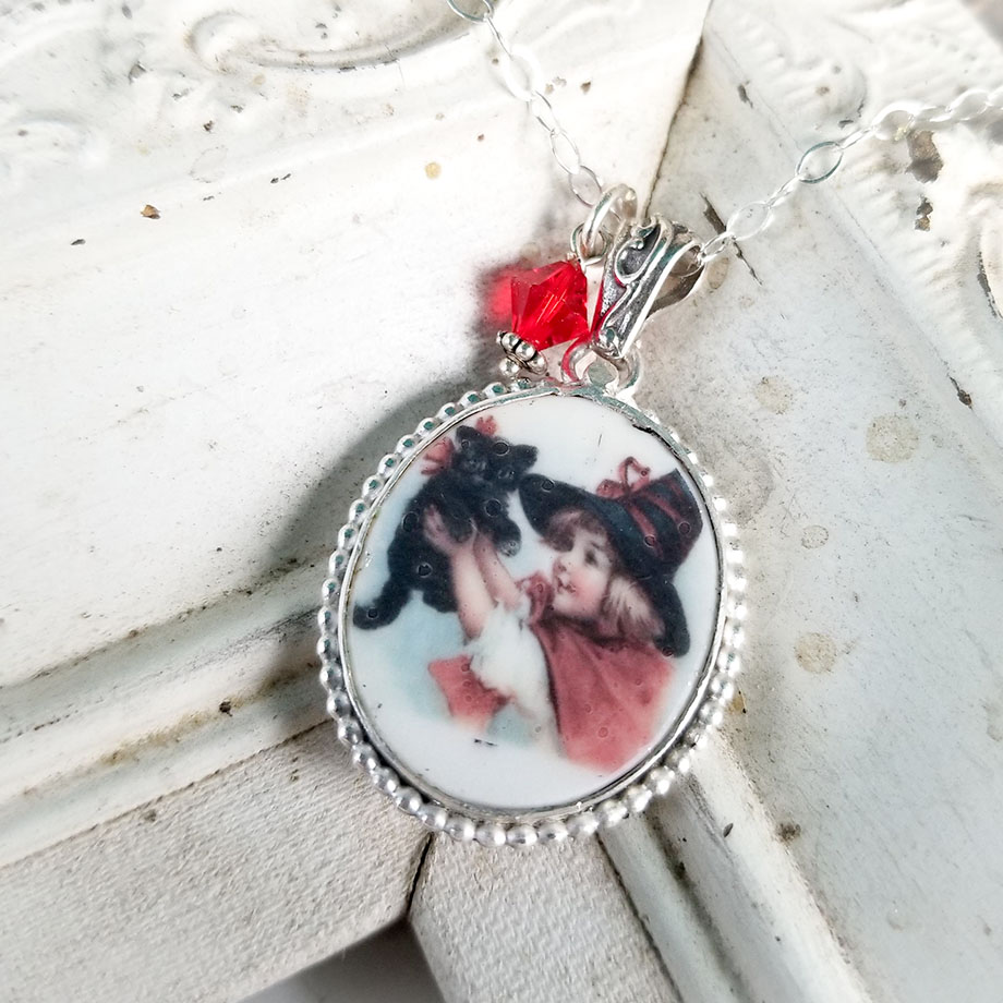 Little Witch holding up Black Kitty Cat Broken China Jewelry Oval Halloween Pendant Necklace